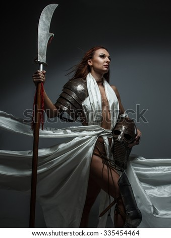 Fantasy woman with sword in white fluttering dress posing in studio over grey background.