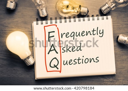 FAQ ( frequently asked questions ) text on notebook with many light bulbs - stock photo