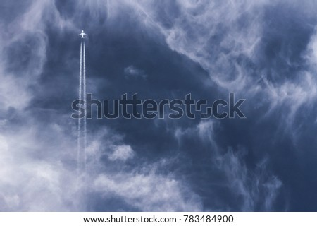 far away air plane with vapor trails going straight up against a deep blue cloudy