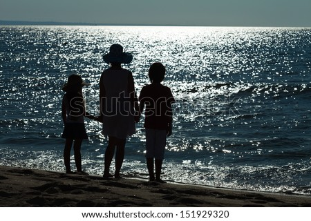Farewell to the sea - woman and kids silhouettes against glittering water surface - stock photo