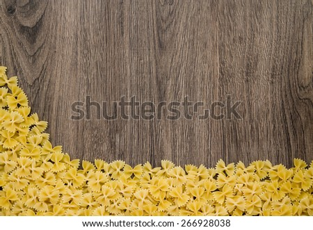 Farfalle pasta lying on a wooden board with the bottom edge of the frame. Top lot of space for text on textured board. - stock photo