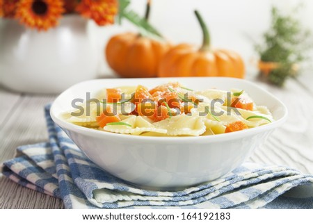 Farfalle pasta with pumpkin and parmesan cheese in a white bowl