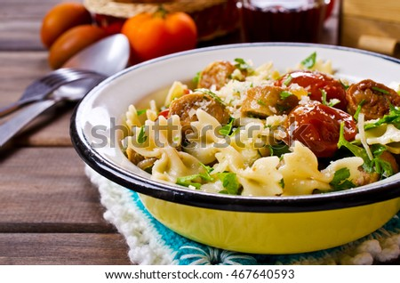 Farfalle pasta with sausage, vegetables and cheese in portion plate. Selective focus.