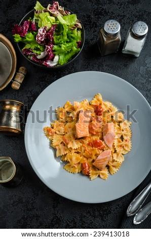 Farfalle with tomato sauce and roasted salmon, fresh endive salad - stock photo