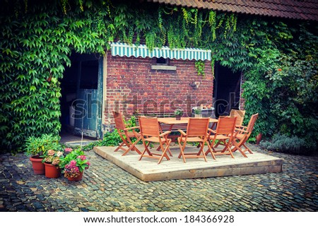 Farm backyard with table and chairs - stock photo