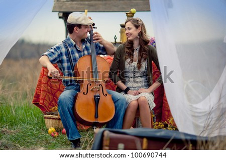 farm boy playing a girl on the cello in the field - stock photo