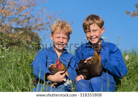 Farm boys sitting in grass with chickens - stock photo