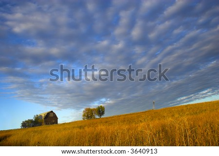 "Farm building with spectacular sky during last moments of the sunset with sign saying ""Little Hill Side Farm""on the background and prairie in the foreground - stock photo"