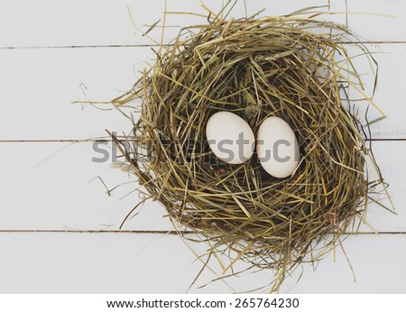 Farm eggs in hay nest on white wooden table background, top view