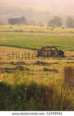 Farm Equipment With Farmhouse In The Distance - stock photo