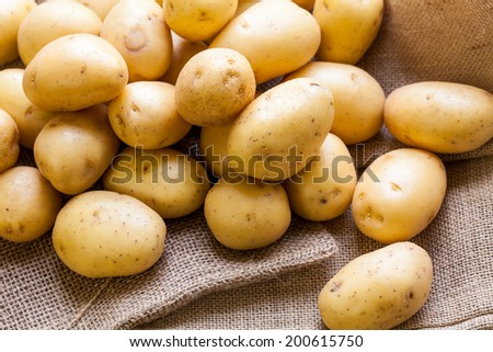 Farm fresh baby potatoes displayed on a hessian sack on a rustic wooden table at farmers market, a healthy nutritious root vegetable popular in vegetarian and vegan cuisine - stock photo