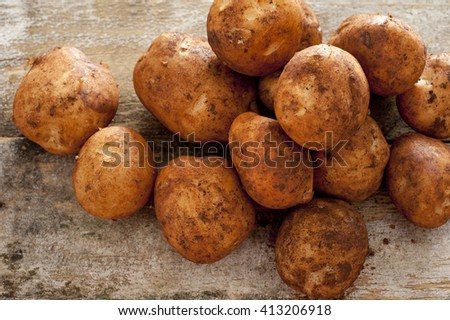 Farm fresh or home grown rustic potatoes covered in dirt in a heap on an old wooden kitchen table, high angle close up view - stock photo