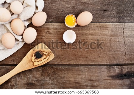Farm fresh organic brown chicken eggs from free range chickens with an old olive wood antique spatula over a rustic wooden background. One egg cracked open showing yolk.