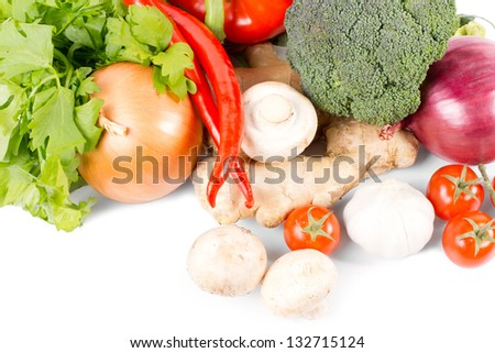 Farm fresh organic vegetables with an assortment of broccoli, mushrooms, chilli peppers, onions, parsley, ginger and tomatos on a white background - stock photo