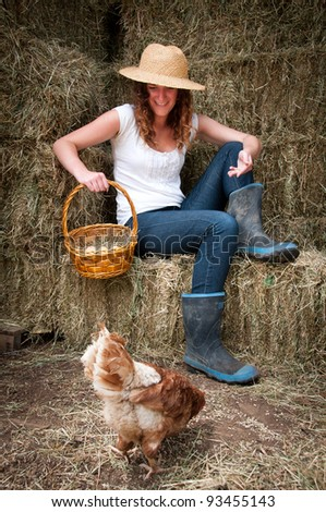 Farm girl in hay barn feeding the chooks and collectiing eggs - stock photo
