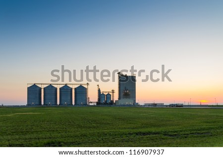 farm grain silos for agriculture after sunset