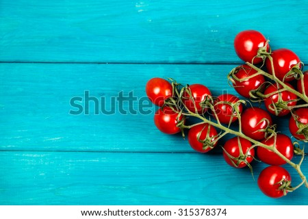 Farm grown cherry tomatos on wooden background. Natural food photography with shallow depth of field. - stock photo