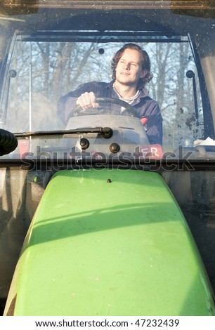 Farm hand behind the wheel of a tractor, seen through the windscreen - stock photo