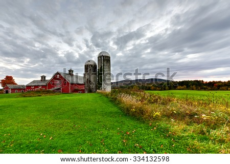 Farm house in Vermont against a dramatic sky during peak foliage in autumn. - stock photo