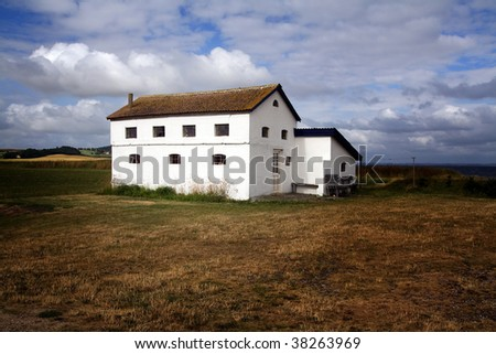 farm house isolated in a field in the countryside . a lonely building in a meadow in denmark - stock photo
