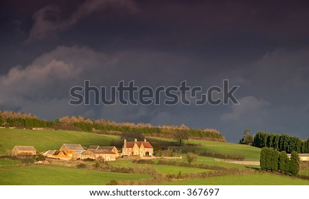 Farm in the countryside with an approaching storm - stock photo