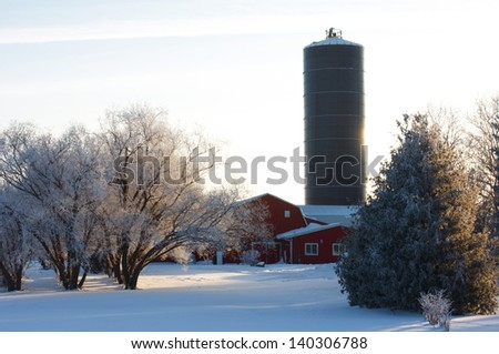 Farm in Winter, with red barn, and silo. - stock photo