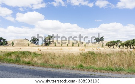Farm land along road with rolls of cut  and baled hay with dry low hills and clouds in sky forming backdrop to field