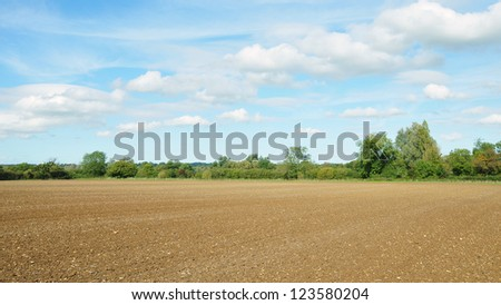 Farm Landscape of Ploughed Earth and a Cloudy Blue Sky Above - stock photo