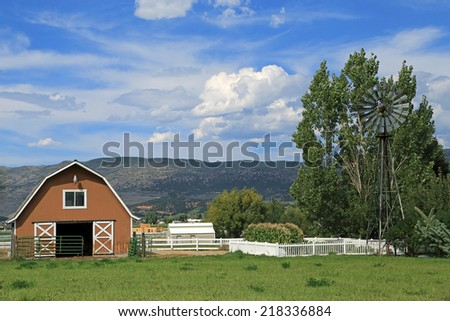 Farm landscape with a barn and a windmill in rural Utah, USA. - stock photo