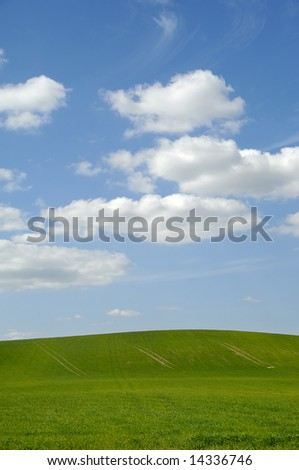 Farm landscape with blue sky and clouds.