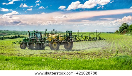 Farm machinery spraying chemicals to the green field. - stock photo