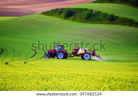 Farm machinery spraying insecticide to the green field, agricultural natural seasonal spring background - stock photo