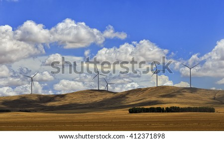 Farm of wind power turbines generating electricity atop of hill range in plains of South Australia on a sunny summer day.
