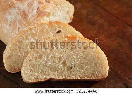 Farm still life. Sliced wheat bread on nice old wooden board - stock photo
