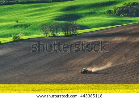Farm tractor handles earth on field - preparing farmland for sowing, agricultural landscape