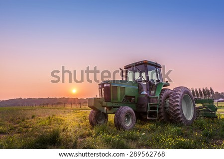 Farm Tractor in a field on a Maryland Farm at sunset - stock photo