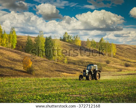 Farm tractor on the field in Europe in the fall - stock photo