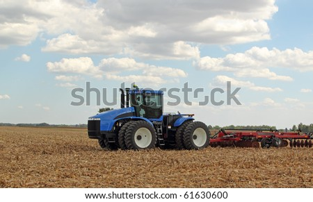 Farm tractor pulling a plow in a harvested corn field - stock photo