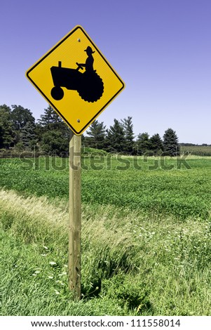 Farm tractor road sign against blue sky - stock photo