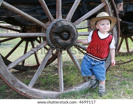 Farmboy:  A baby cowboy hangs out at the wheel of an old farm wagon in a cowboy hat and denim shorts. - stock photo