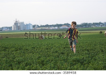 farmboy running through clover field with hay, room in sky for text - stock photo
