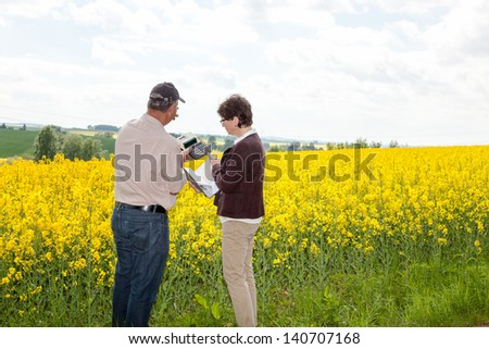 Farmer and Agraringeniuer discuss the rape field - stock photo