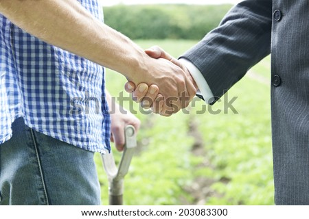 Farmer And Businessman Shaking Hands - stock photo