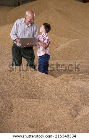 Farmer and grandson holding laptop on wheat grain heap - stock photo