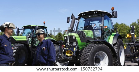 farmer and mechanic with large tractors in background, latest models - stock photo