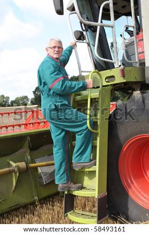 Farmer climbing on harvest machine - stock photo