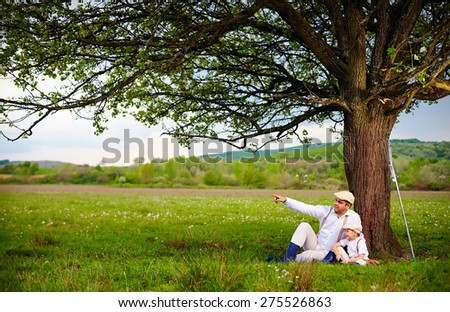 farmer father and son sitting under the tree, spring countryside
