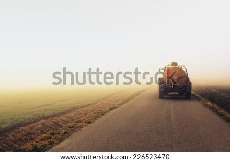 Farmer goes car morning Autumn road in the fog - stock photo