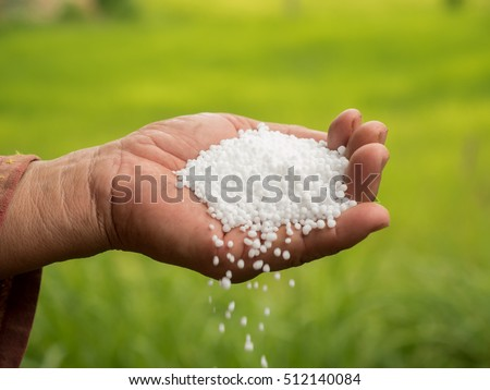 Farmer hand pouring plant chemical urea fertilizer over green background