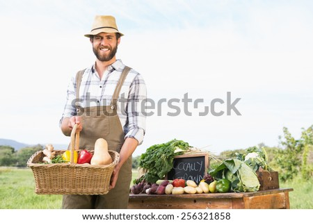 Farmer holding basket of vegetables at market on a sunny day - stock photo
